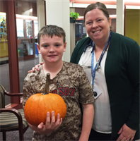 Butler student Kellen who guessed the pumpkin weight, and Nurse Lisa Harteveldt during PACK week